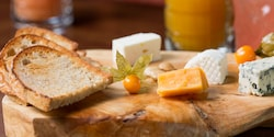 A variety of cheeses and bread on a wooden cutting board