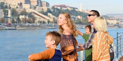 A family of Guests gaze out over the water as they ride a boat past the majestic buildings onshore