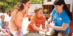 An Adventure Guide helps a young boy stir a vat while his mom watches
