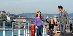 Parents and their young daughter laugh while walking on the ship's deck as they sail past Budapest