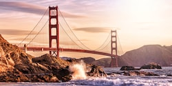 The sun shines over San Francisco's Golden Gate Bridge as water crashes against the rocks