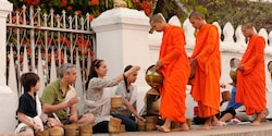 Monks collect daily alms from seated tourists