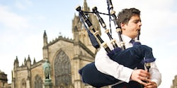 A man plays the Bagpipe while standing in front of a castle
