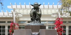 A statue of Yoda atop a fountain outside an office building