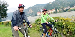 A pair of Guests ride bikes along a riverbank in front of rolling hills and historic buildings