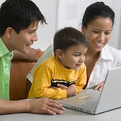 A smiling mother, father and young son looking at the screen of an open laptop computer