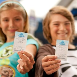 Two kids hold up FASTPASS tickets to Star Tours