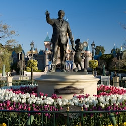 A statue of Walt Disney holding Mickey's hand called 'Partners' and, beyond, a castle
