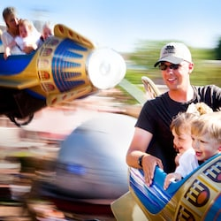 A father and his 2 young children ride Dumbo the Flying Elephant at Disneyland Park