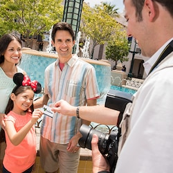 With her parents, a girl wearing Minnie ears hands her PhotoPass card to a photographer at Carthay Circle fountain