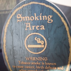 A round wooden sign designating a smoking area with health warning