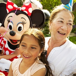 Minnie Mouse joins a grandmother and granddaughter at a birthday celebration