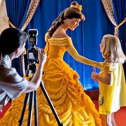 Photographer prepares to take a picture of Belle and a girl at the Enchanted Tales with Belle attraction