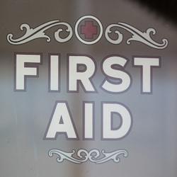 "A glass window imprinted with the words ""First Aid"" and a red cross"
