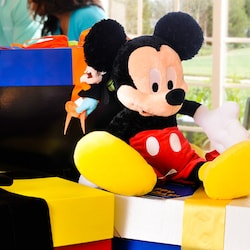 Colorful gift-wrapped boxes with a big plush Mickey Mouse sitting on top