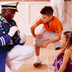 Cast Member in a uniform shows his pin collection to a boy and girl