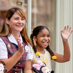 A Disney Cast Member in a Guest Relations uniform with a young female Guest, both waving
