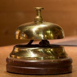 An old service bell on a wooden desk