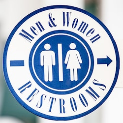 A circular sign directs Guests toward the location of separate restrooms for both men and women