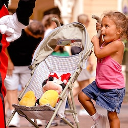 Little girl holding a handle of a stroller while looking up at Mickey Mouse