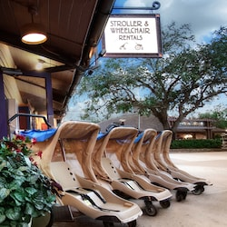 Strollers line the exterior of a stroller and wheelchair rental location at Walt Disney World Resort