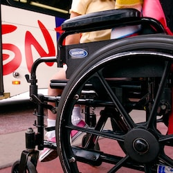 Partial side view of a wheelchair holding a little girl