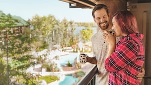 A smiling couple stand with mugs on a balcony above a pool area