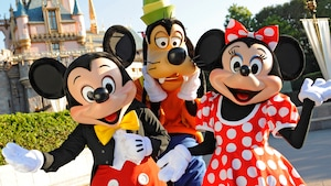 Mickey, Goofy and Minnie stand together near Sleeping Beauty Castle