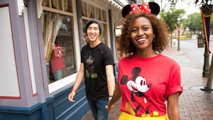 A young man holds hands with a woman wearing a Mickey T shirt and a Minnie ear headband