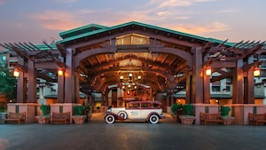 A vintage car sits outside the craftsman style main entrance to the Grand Californian Hotel