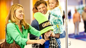 A mom pulls on the long ears of her sons Goofy hat while the dad holds his young daughter
