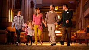 A mom, dad, teen son and young daughter walk through the Grand Californian lobby with a Cast Member