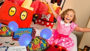 A little girl in a polka dotted dress sits on a bed with Mickey ears hats, bags sunglasses and books