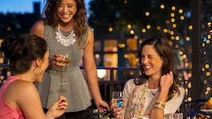 Three women laugh, talk and drink wine at an outdoor table with twinkling trees in the background