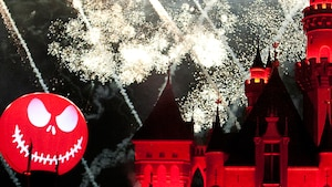 The Halloween Screams fireworks go off behind Sleeping Beauty Castle and a Jack Skellington decoration