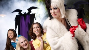 3 girls share a laugh in reaction to a sneering Cruella DeVille, while a bat figure approaches them