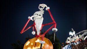 A Jack Skellington figure dressed as Santa Claus contemplates a snowflake while sitting atop a pumpkin