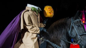 The Headless Horseman holds a jack o lantern while riding a horse