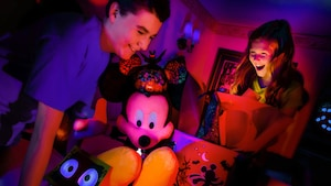 A young boy and girl smile in delight in a darkened room decorated with Halloween treats and a large Mickey Mouse plush