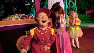 A young boy dressed as a racecar driver smiles in delight while a small girl dressed as a princess admires an assortment of Halloween treats