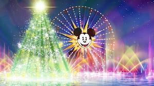 An illuminated Christmas tree and Mickey's Fun Wheel amid erupting fountains
