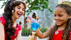 A little girl wearing a tiara touches a blue scepter as Princess Elena of Avalor smiles on