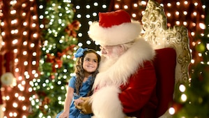 A little girl smiles atop Santa's lap