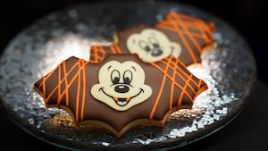 Chocolate iced cookies in the shape of a bat featuring the face of Mickey Mouse with vampire fangs