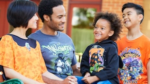 A mother, father and their young son and daughter wear Halloween themed, Disney tee shirts