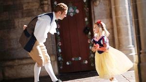 Uma menina, vestida como Snow White, cumprimenta um amigo real