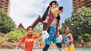 Uma menina e um menino de mãos dadas com o Goofy na piscina do Disney Aulani Resort and Spa.