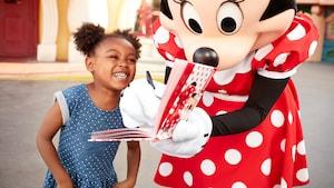 Uma menina sorri enquanto a Minnie Mouse assina o livro de autógrafos dela.