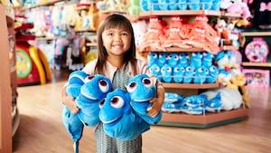 Uma menina segurando 4pelúcias da Dory em uma loja da Disney