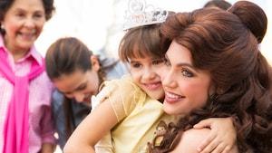 Une petite fille portant un diadème sourit dans les bras de Belle.